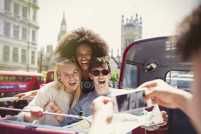 Enthusiastic friends being photographed on double-decker bus — Stock Photo
