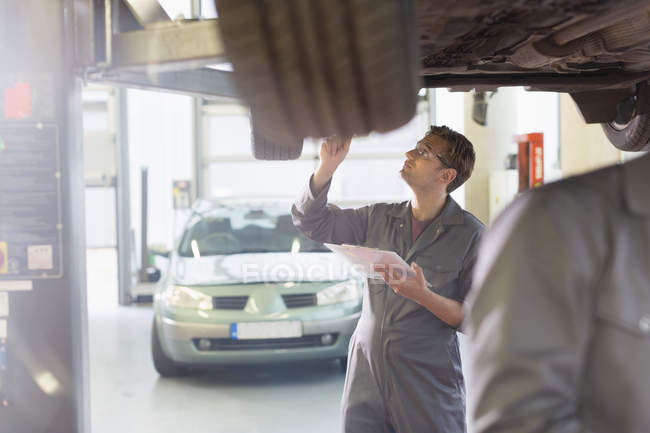 Mechanic with clipboard under car in auto repair shop — Stock Photo