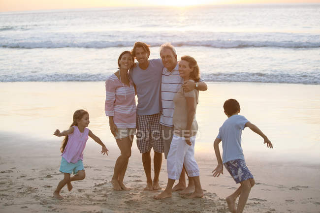 Multi-generation family hugging on beach — Stock Photo