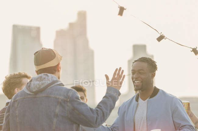 Young men high fiving at rooftop party — Stock Photo
