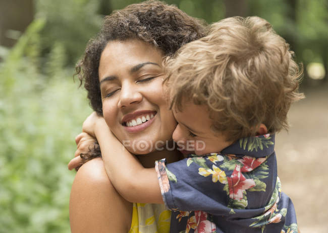 Close up affectionate mother and son hugging with eyes closed — Stock Photo