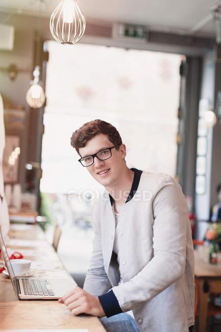 Ritratto uomo sorridente con occhiali da vista utilizzando il computer portatile in caffè — Foto stock
