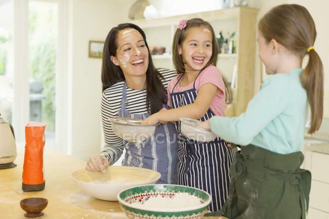 Смеющиеся мать и дочери пекут с мукой на лицах на кухне — стоковое фото