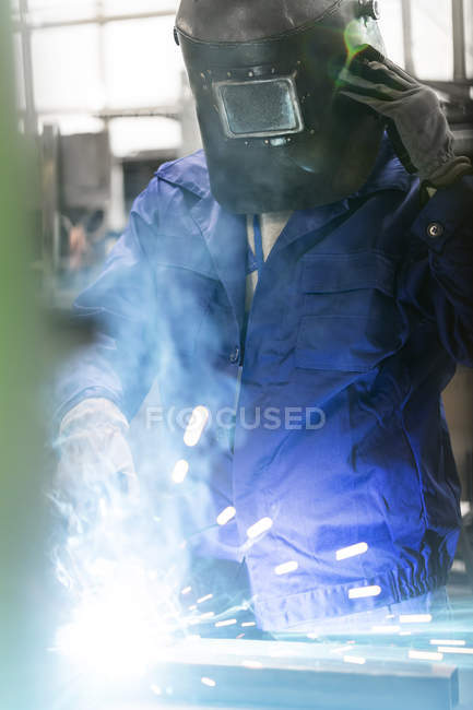 Welder in protective workwear working in factory — Stock Photo