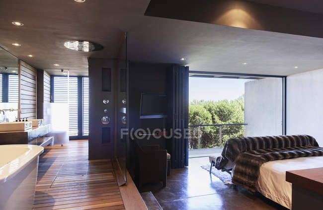 Glass wall separating master bedroom and bathroom — Stock Photo