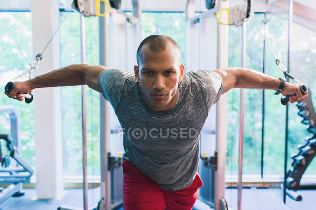 Determined man doing cable chest fly at gym — Stockfoto