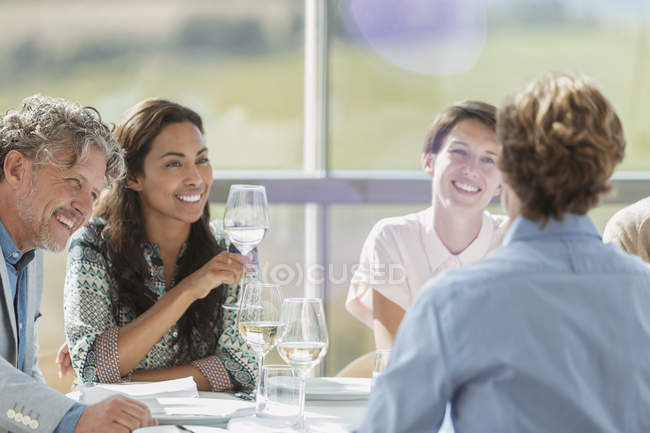 Friends drinking wine and talking at restaurant table — Stock Photo