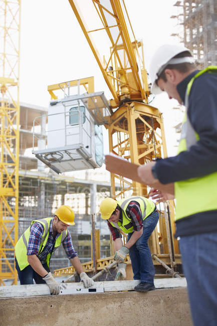 Trabalhadores da construção usando ferramenta de nível abaixo do guindaste no canteiro de obras — Fotografia de Stock