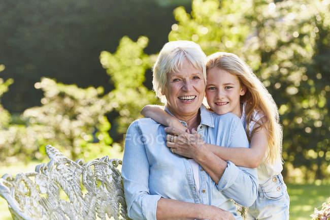 Portrait smiling grandmother and granddaughter hugging in garden — Stock Photo