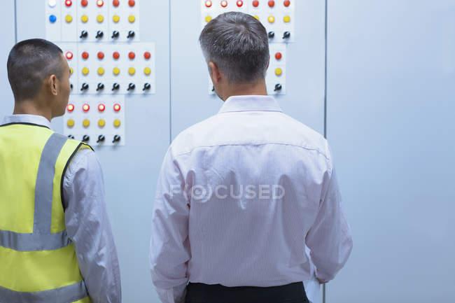 Supervisore e lavoratore presso il pannello di controllo in fabbrica — Foto stock