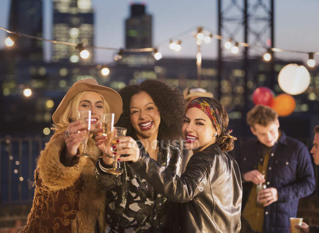 Portrait enthusiastic young adult friends toasting champagne flutes at nighttime rooftop party — Stockfoto