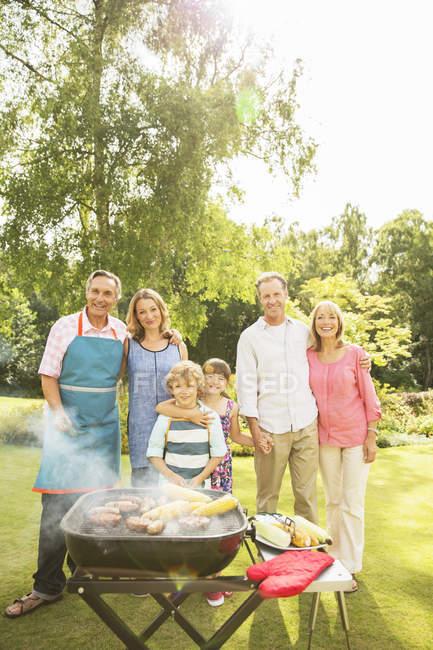 Семья из нескольких поколений стоит на барбекю на заднем дворе — стоковое фото