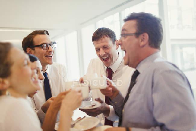 Les gens d'affaires riant et buvant du café au bureau — Photo de stock