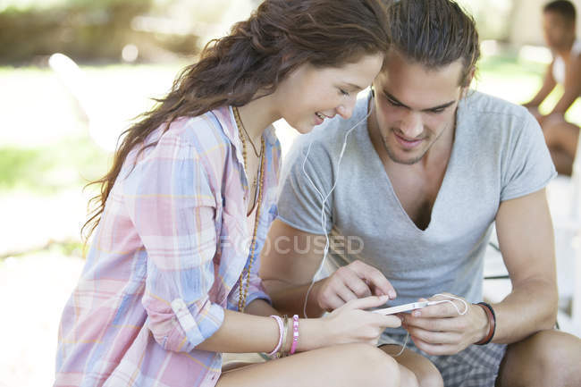 Couple listening to mp3 player outdoors — Stock Photo