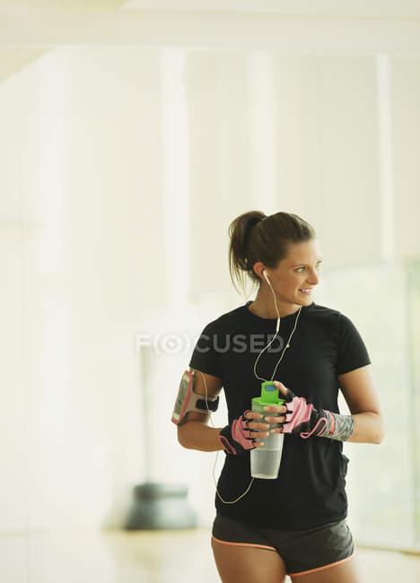 Femme souriante prenant une pause d'eau potable dans le studio de gym — Photo de stock