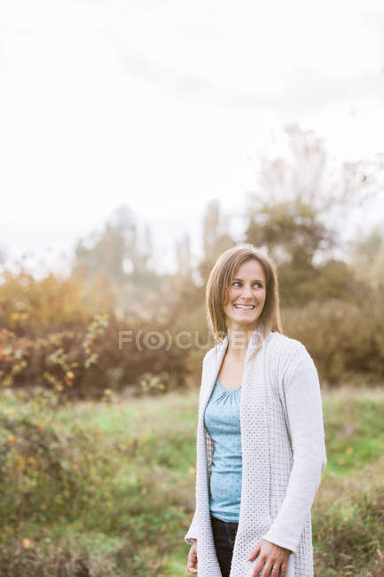 Smiling woman looking away in autumn park — Stock Photo
