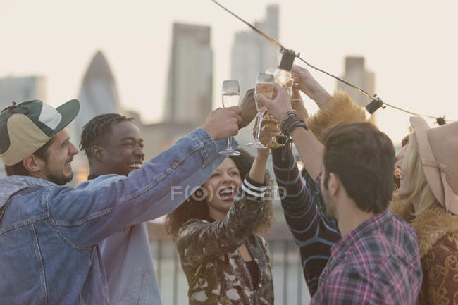 Young adult friends toasting champagne glasses at rooftop party — Stockfoto