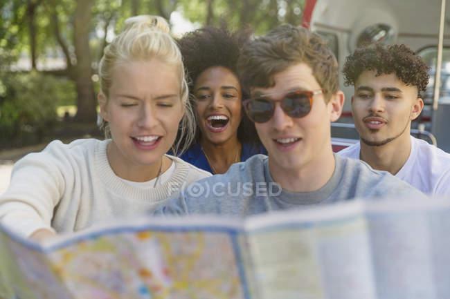Друзья смотрят на карту на двухэтажном автобусе — стоковое фото