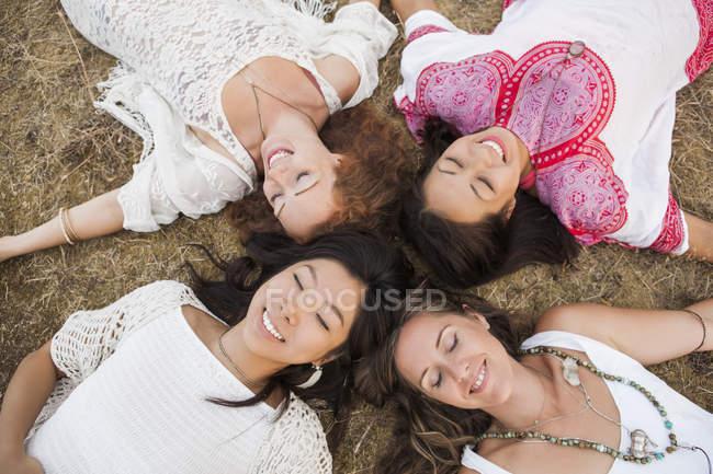 Vue aérienne de femmes boho souriantes couchées en cercle avec les yeux fermés — Photo de stock