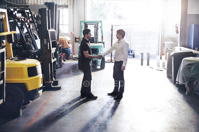 Mechanic and customer handshaking in auto repair shop — Stock Photo