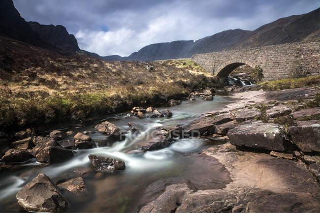 Torrente che scorre sotto remoto acquedotto, Scozia — Foto stock