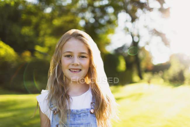 Portrait smiling girl in sunny garden — Stock Photo