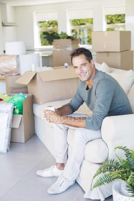 Portrait of smiling man enjoying coffee on sofa among cardboard boxes — Stock Photo