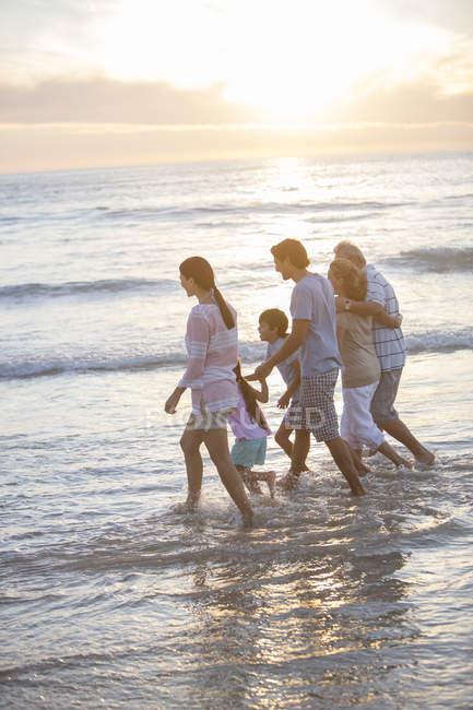 Семья из нескольких поколений, гуляющая в серфинге на пляже — стоковое фото