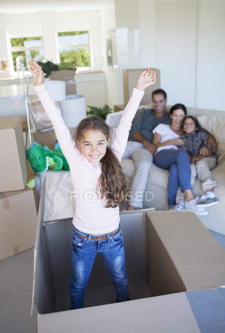 Girl playing inside cardboard box in new house — Photo de stock