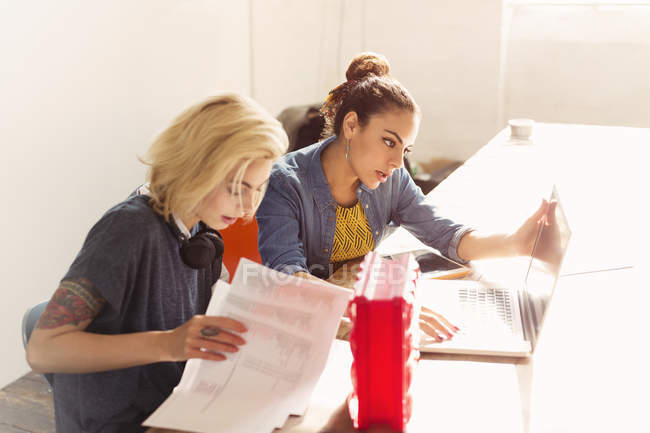 Creative young businesswomen with laptop and paperwork in office — Stock Photo