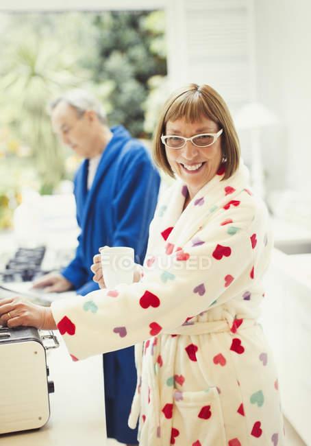 Портрет улыбающейся зрелой женщины, пьющей кофе в халате за кухонным столом — стоковое фото
