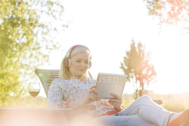 Donna anziana con cuffie e vino utilizzando tablet digitale sulla sedia a sdraio nel cortile soleggiato — Foto stock