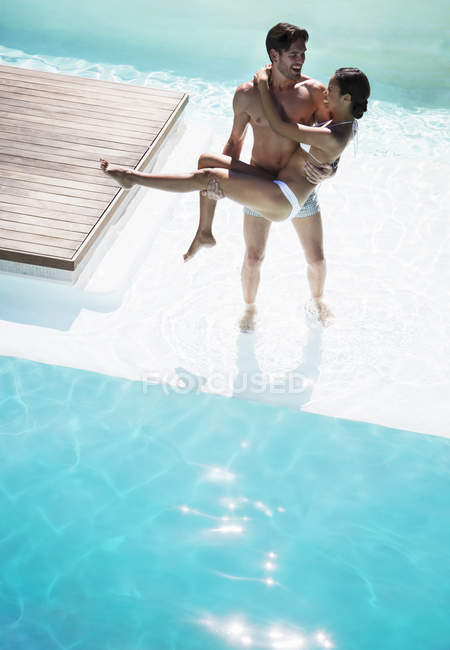 Young attractive couple relaxing in swimming pool — Stock Photo