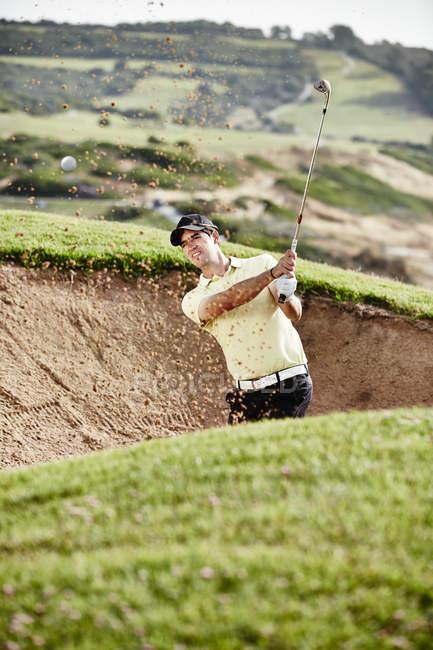 Homme, oscillant entre la fosse de sable sur le terrain de golf — Photo de stock