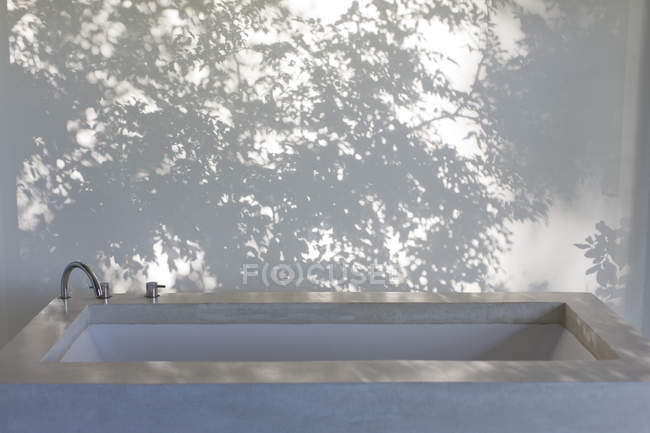 Sombras de árboles en la cortina detrás de la bañera - foto de stock