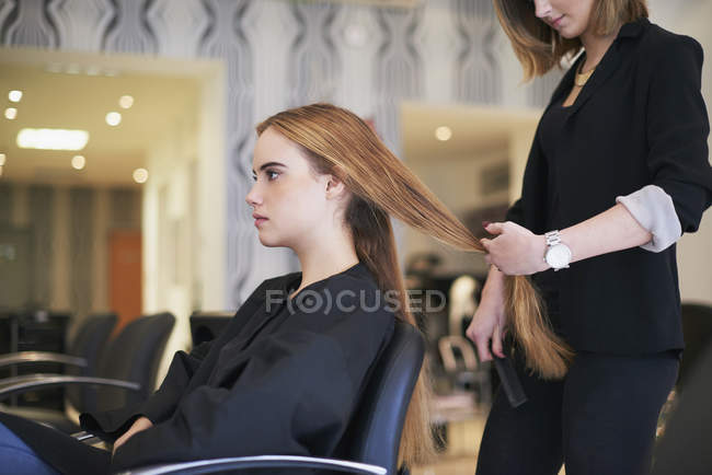 Hairdresser preparing to cut customers long hair in salon — Stock Photo