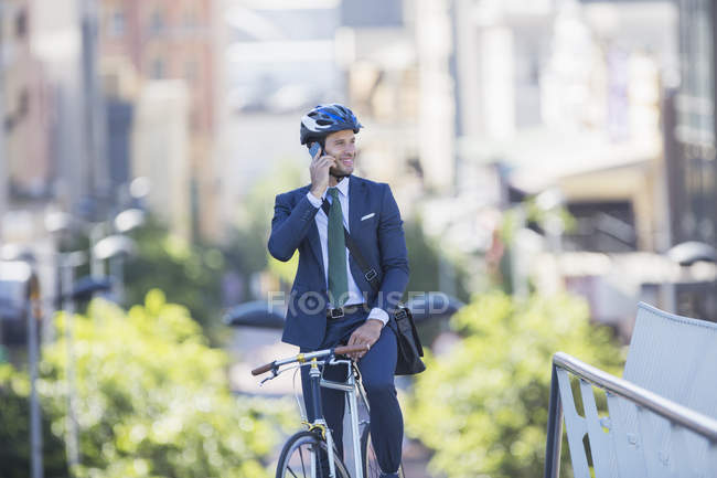 Businessman in suit and helmet sitting on bicycle talking on cell phone in city — Stock Photo