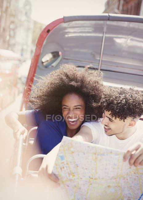 Begeisterten Paar mit Karte im Doppeldecker-bus — Stockfoto