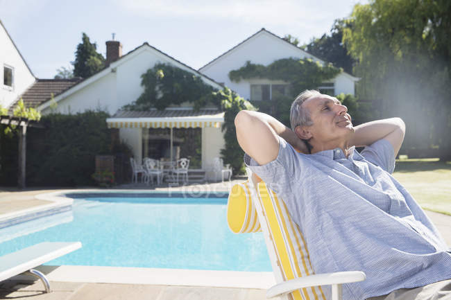 Man relaxing in lounge chair at poolside — Stock Photo