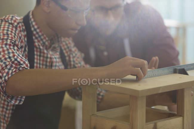 Основное внимание плотники измерения древесины с правителем в мастерской — стоковое фото