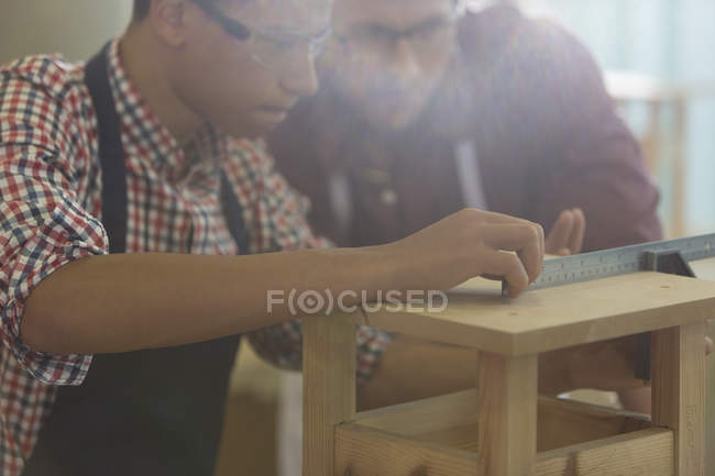 Focused carpenters measuring wood with ruler in workshop — Stock Photo