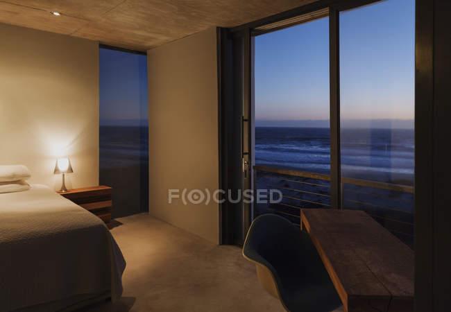 Moderne Schlafzimmer mit Blick auf Meer in der Abenddämmerung — Stockfoto