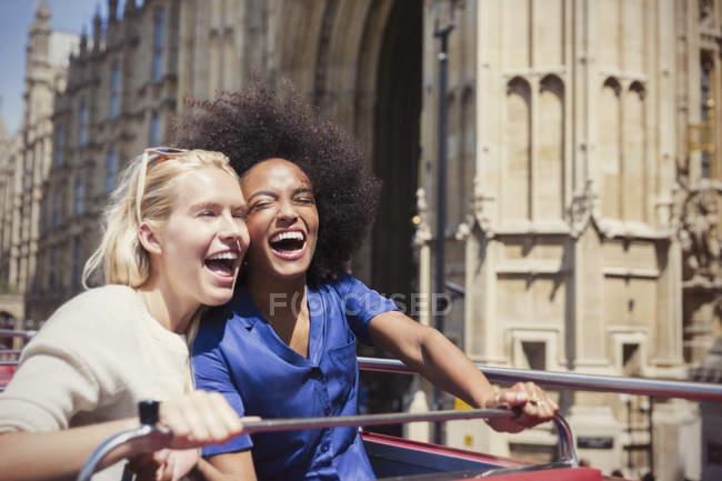 Des amis enthousiastes rient dans un bus à deux étages à Londres — Photo de stock