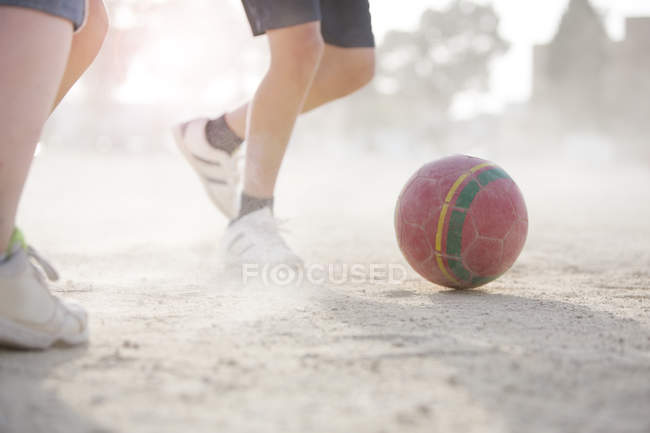 Children playing with soccer ball in sand — Stock Photo