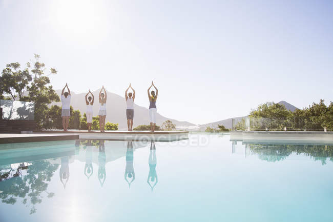 Young attractive people practicing yoga at poolside — Stock Photo