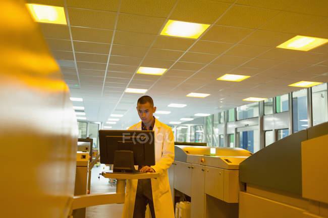 Arbeiter im Laborkittel am Computer zwischen Druckern in der Druckerei — Stockfoto