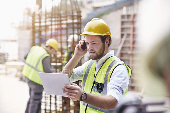 Engineer with digital tablet talking on cell phone at construction site — Stock Photo