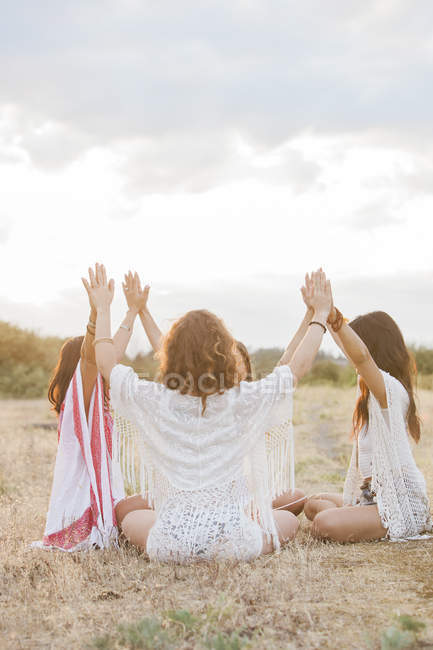 Boho women sitting in circle with arms raised and connected in rural field — Stock Photo