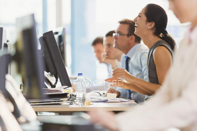 Смеющаяся деловая женщина, работающая за компьютером в офисе — стоковое фото