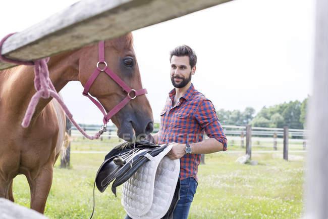Homem removendo sela de cavalo em pasto rural — Fotografia de Stock